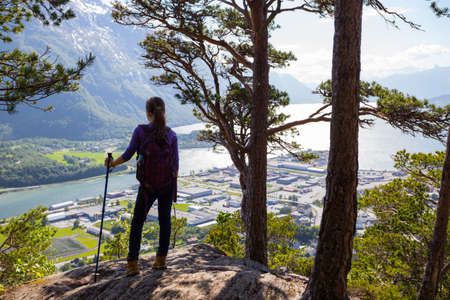 trekking pole: girl hiker with a backpack and trekking pole standing and looking on Romsdalsfjorden and Andalsnes, Norway