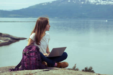 hardangerfjord: girl hiker with a laptop sitting on a rock on a background of mountains and lakes, norway
