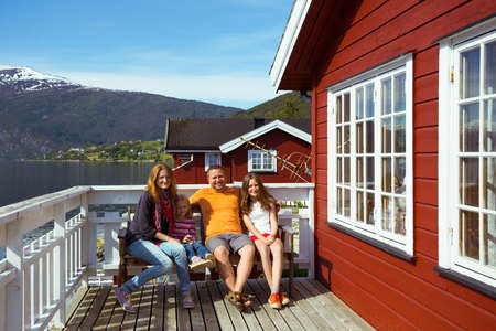 rorbu: happy family sitting near rorbu. beautiful Norwegian landscape at the fjord and mountains, norway Stock Photo
