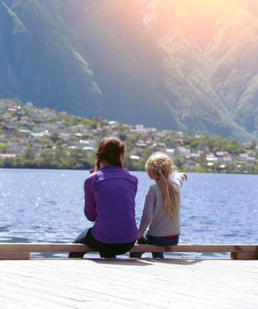 admires: girls on the bank and admires the beautiful Norwegian landscape at the fjord and mountains