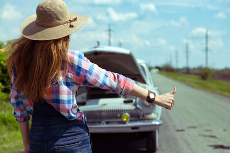 hitch hiker: young woman hitch-hiking on a road at the fields