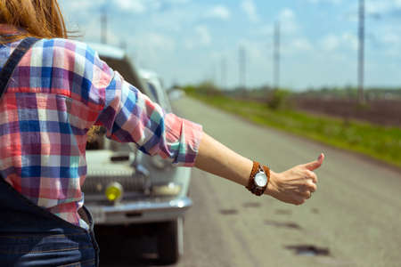 hitchhiking: young woman hitch-hiking on a road at the fields