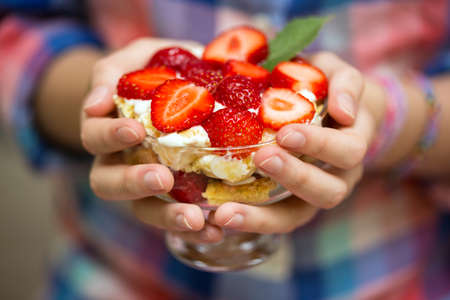 garnished: girl holding dessert garnished with strawberries Stock Photo