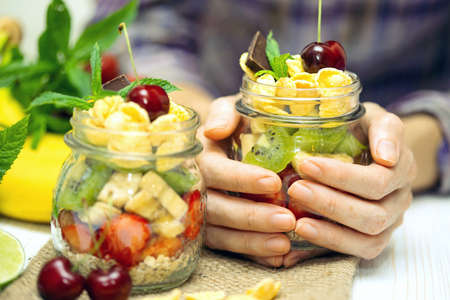 cereals holding hands: healthy diet. girl holding oatmeal with berries and fruits Stock Photo