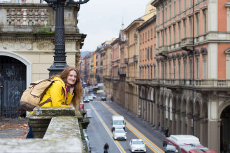 parapet: girl standing near parapet and looking at the Bologna streets