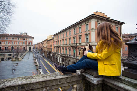 girl sitting on a parapet and looking at the Bologna streets Stock Photo