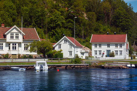 traditional norwegian wooden house to stand at the lakeside and mountains in the distance, norway Stock Photo