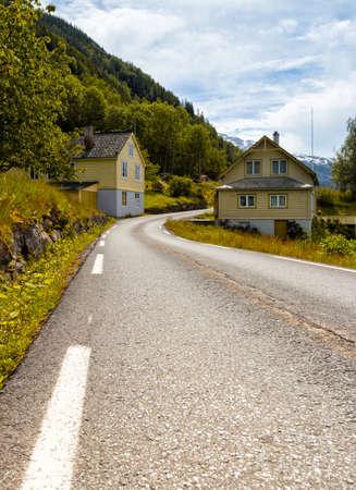 alongside: road passes alongside traditional Norwegian wooden houses, Norway