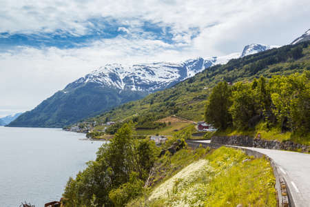 divide: road along the shore of the fjord at the norwegian mountains, Norway Stock Photo