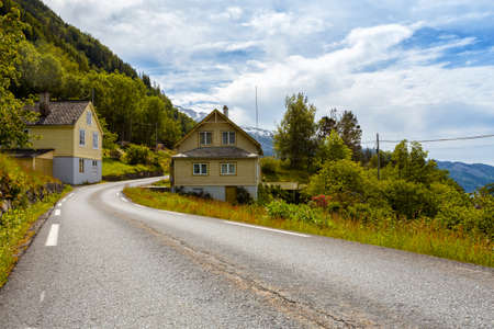 road passes alongside traditional Norwegian wooden houses, Norway