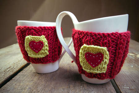 table scraps: Knitted woolen cups on a wooden table