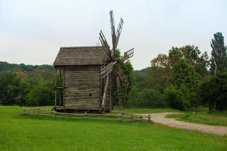 old wooden wind mill on a grass lawn