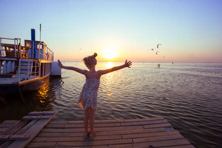 spit: Girl on the pier in the background of the sea, ship and sunset. Ukrainian landscape Stock Photo