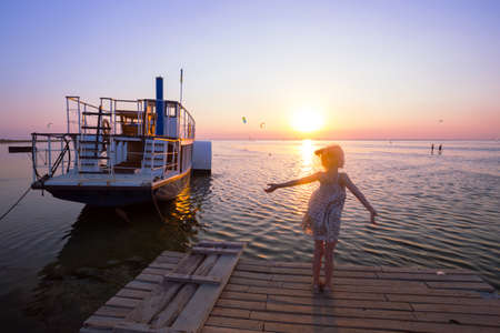 azov: Girl on the pier in the background of the sea, ship and sunset. Ukrainian landscape Stock Photo