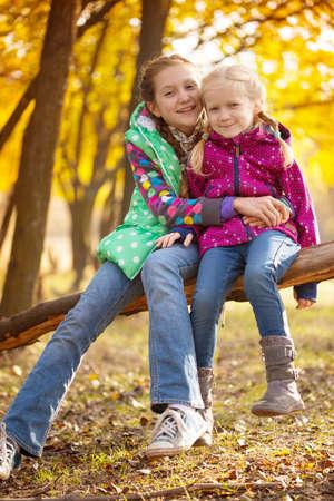 retrato de las niñas sonrientes hermanas en el bosque de otoño