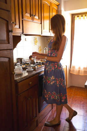 coffeepot: Breakfast - girl in the kitchen pouring coffee in a cup from the coffeepot Stock Photo