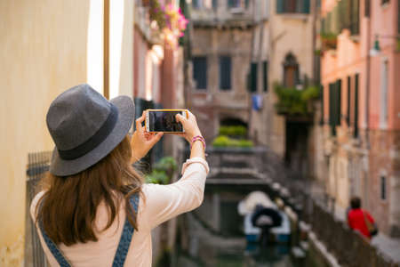 girl taking a photo of ancient streets and canals of Venice with smartphone in Italy photo