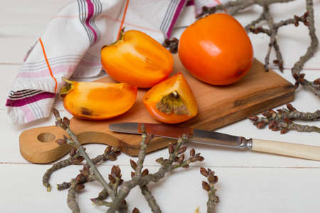healthy food. Two persimmons are on the board, a knife and a towel Stock Photo