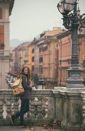 parapet: girl standing near parapet and looking at the camera, Bologna. italy
