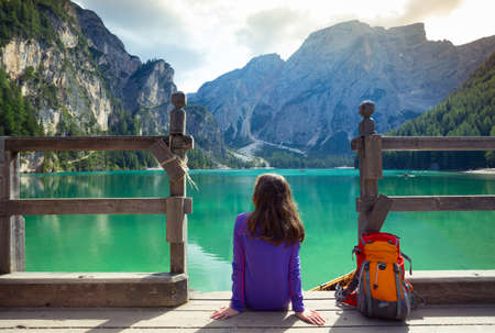 di: girl backpacker sitting on a pier and looking at Braies lake  Stock Photo