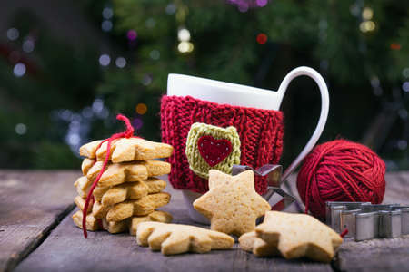 table scraps: christmas - knitted woolen cups and star shaped gingerbread on a wooden table Stock Photo