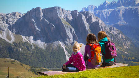 family - mother and two sisters girls hikers sitting on the bench at the mountains Dolomites, Italy. Seceda