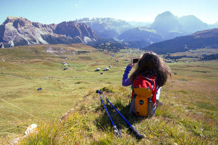 girl hiker taking a photo on a smartphone at the mountains Dolomites and views of the valley, Italy. Seceda