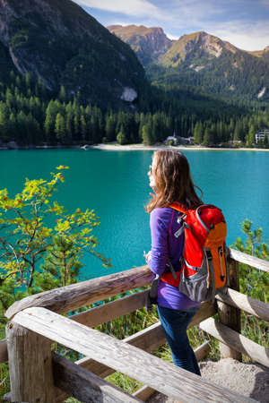girl backpacker standing on a trail and looking at Braies lake, Dolomites Italy