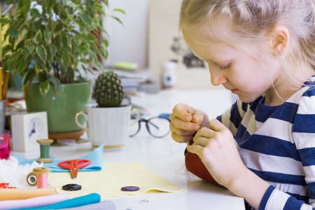 table scraps: creation. little girl sews toy made of felt