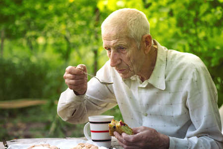 aging: portrait of senior man sits in the garden and drinks tea with a pie Stock Photo
