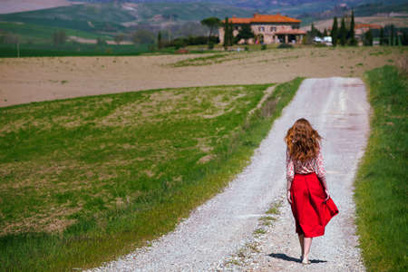 girl is walking along the road among the fields and a typical Tuscan landscape behind her. Tuscany, Italy