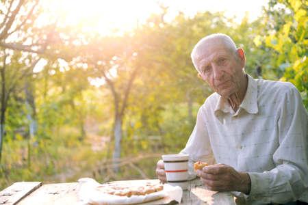 aging: portrait of smiling senior man sits in the garden and drinks tea with a pie