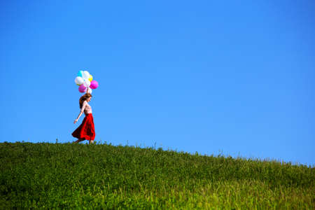 Happy girl in the meadows tuscan with colorful balloons, against the blue sky and green meadow. Tuscany, Italy