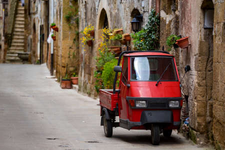Piaggio Ape standing at the empty street of old italian town Stock Photo