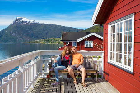 happy couple on a wooden terrace with the beautiful fjord at the background
