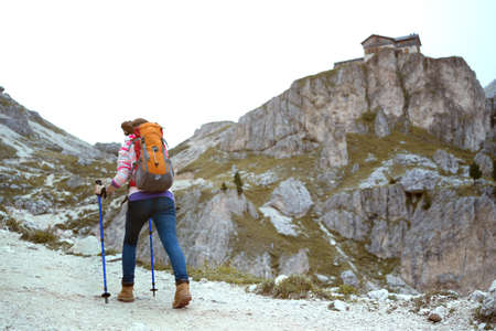 girl hiker at the mountains Dolomites, view of the  Rifugio Vajolet, Pozza Di Fassa, Italy