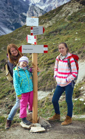 di: family - mother and two daughters  girls sisters hikers  standing near sign for direction at the mountains Dolomites, Italy. Tre Cime di Lavaredo