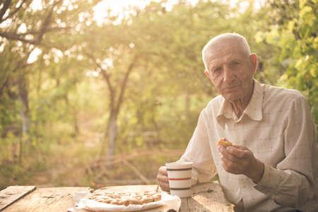 granddad: senior man drinking a tea at the garden