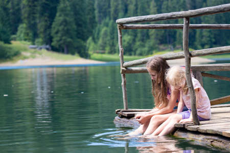 dipping: children on a wooden pier with the legs dipped into the pond Stock Photo