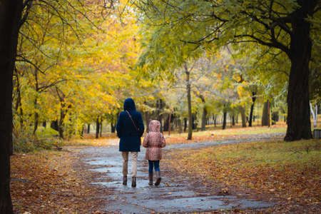 mother and daughter walking after the rain at the autumn park Stock Photo