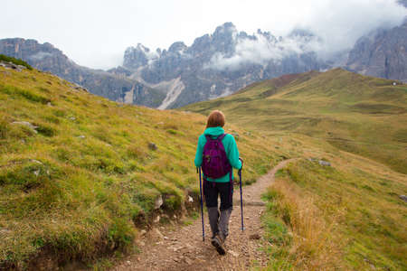girl hiker on a trail at the Dolomites mountains