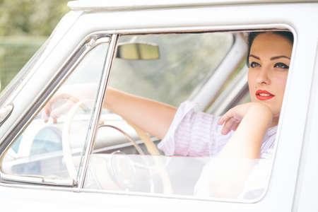 Porträt des schönen Mädchens in einem Retro- Auto im Artstift oben Standard-Bild - 83534992
