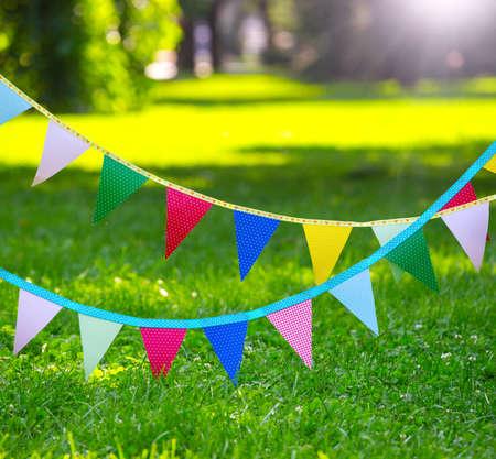Bandiere di festa colorate fatte di carta sullo sfondo di un prato verde Archivio Fotografico - 84448292