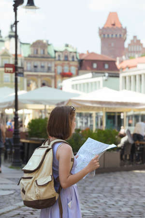 girl looking at the map standing at the main square Rynek of polish city Poznan Stock Photo