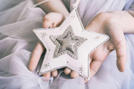 Kerstmis - de handen van kinderenmeisje die een ster houden Stockfoto - 85359859