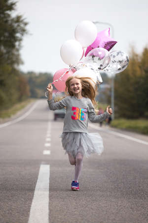birthday - happy girl with balloons run along the dividing strip of the road