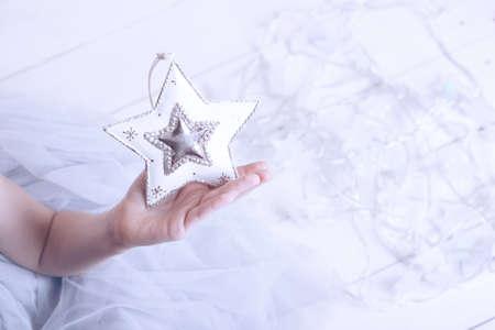 Kerstmis - de handen van kinderenmeisje die een ster houden Stockfoto - 90324442