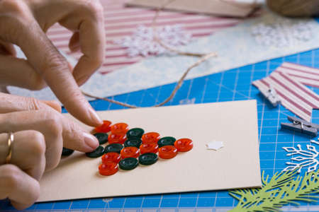 scrapbook background. Girl make christmas postcard from buttons and tools with decoration