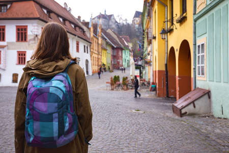 girl hipster walking at the beautiful street in the old town of Sighisoara, Romania