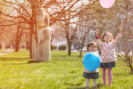 little smiling sisters girls with balloon in the park. Spring Stock Photo